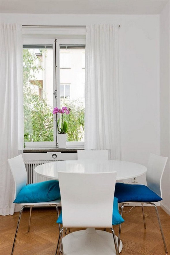 a small dining table with turquoise cushions an intriguing looking coffee table and exit towards the balcony