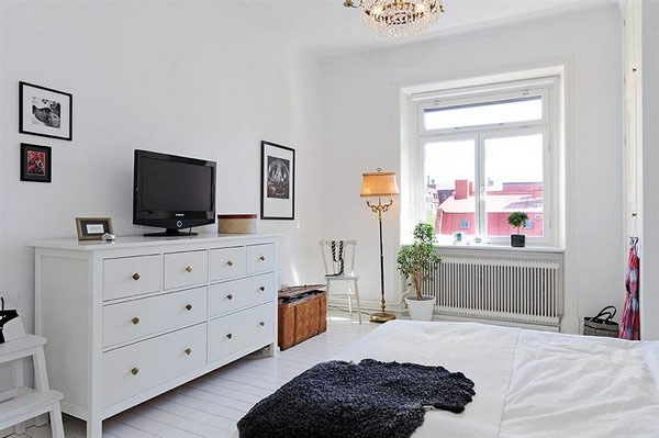 A large window facing a beautiful garden and a king-sized bed makes this room the optimum sleeping interior of the apartment with Vintage Elements and Extreme Space